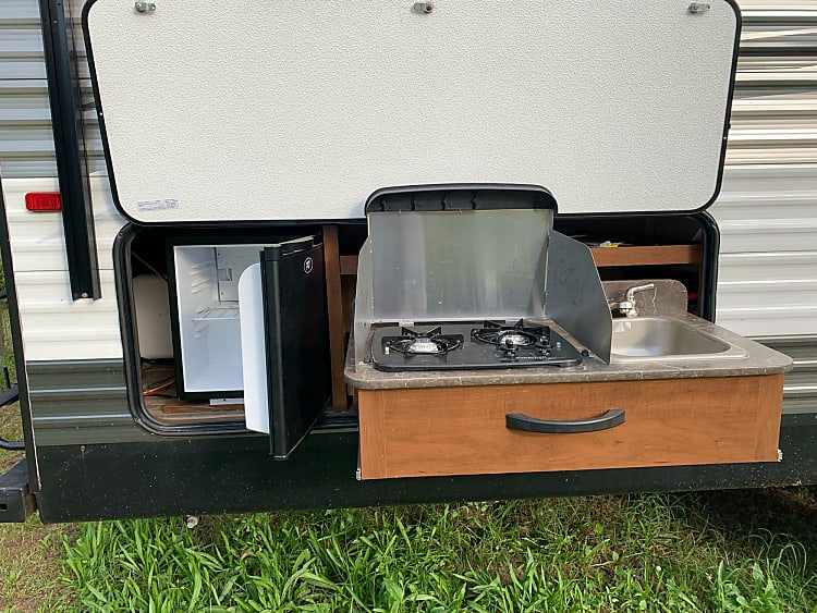 Out door Kitchen. Features two burner stove, sink, and mini fridge.