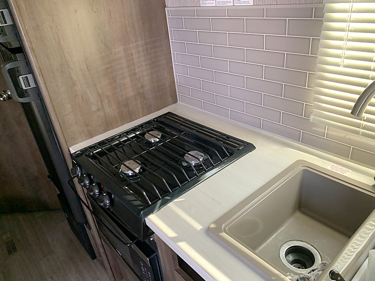 Kitchen Stove, and kitchen sink. Microwave built in below stove top