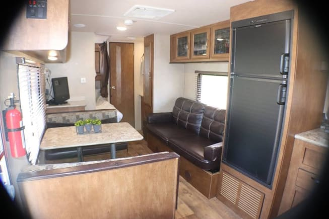 Couch and kitchen table that both will make into additional bedding. TV, interior and exterior speakers, and DVD player. Plenty of interior storage.