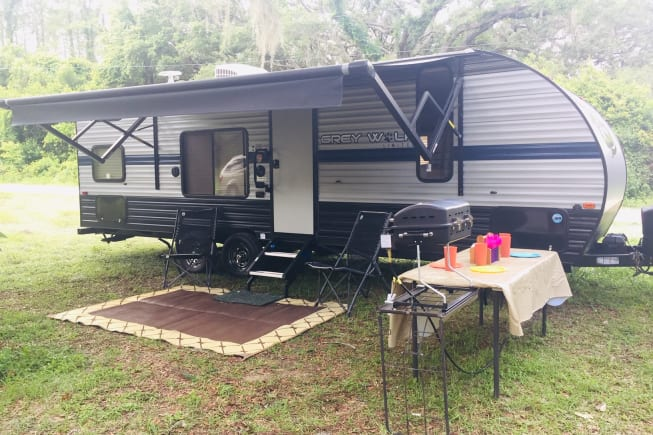 Travel trailer setup with awning, chairs and grill