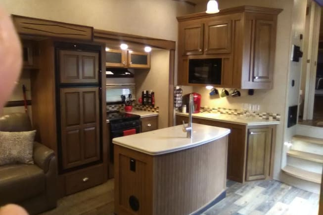 Beautiful kitchen with center island, coffee station, 3 burner stove, good size refrig/freezer,  dishes, pots/pans.