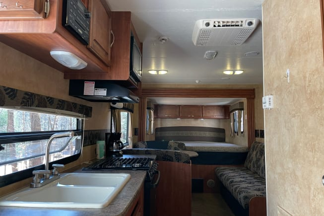 Double sink, radio, air conditioner, range, and stove vent.