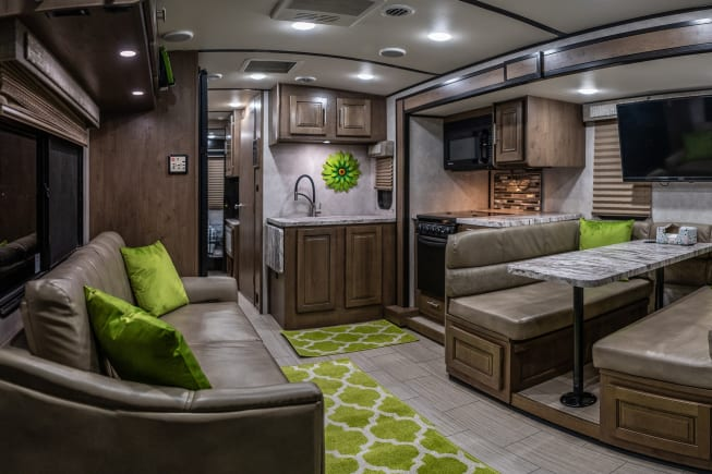 Spacious, modern living area and kitchen. Couch has (2) recliners, and folds into a bed. Dinette also turns into a bed.