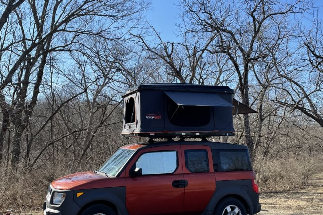 """Doesn't she look like fun? This is our Element Micro Camper, """"Orange You Glad"""" with the roof-top tent set up to camp."""