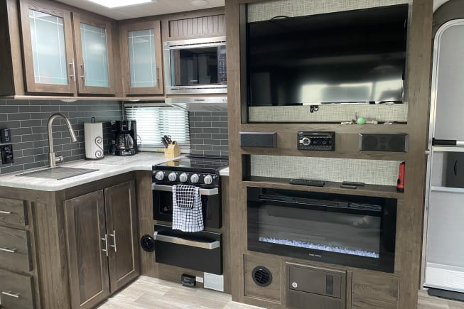"""Fully equipped kitchen with sink, stove, oven, microware.  Entertainment space includes 32"""" TV/DVD system w/ electric fireplace."""