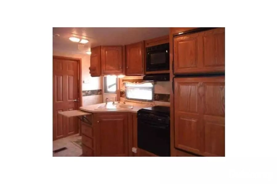 2 Bedroom 1.5 Bath 30ft Dual Slide Out Ready To Camp Westland, MI Beautiful kitchen with view of the front entry and the large screen tv should you wish to watch a show while preparing your meals on the propane stove.  The counter expands and flips down for storage.