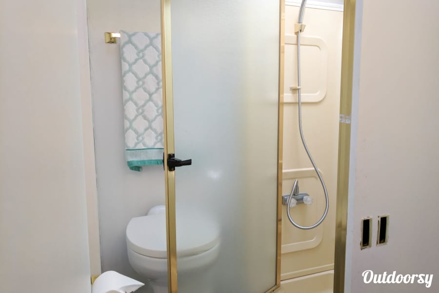 Peggy, our 1995 Fleetwood Flair Montebello, California shower and toilet. Toilet is porcelain.