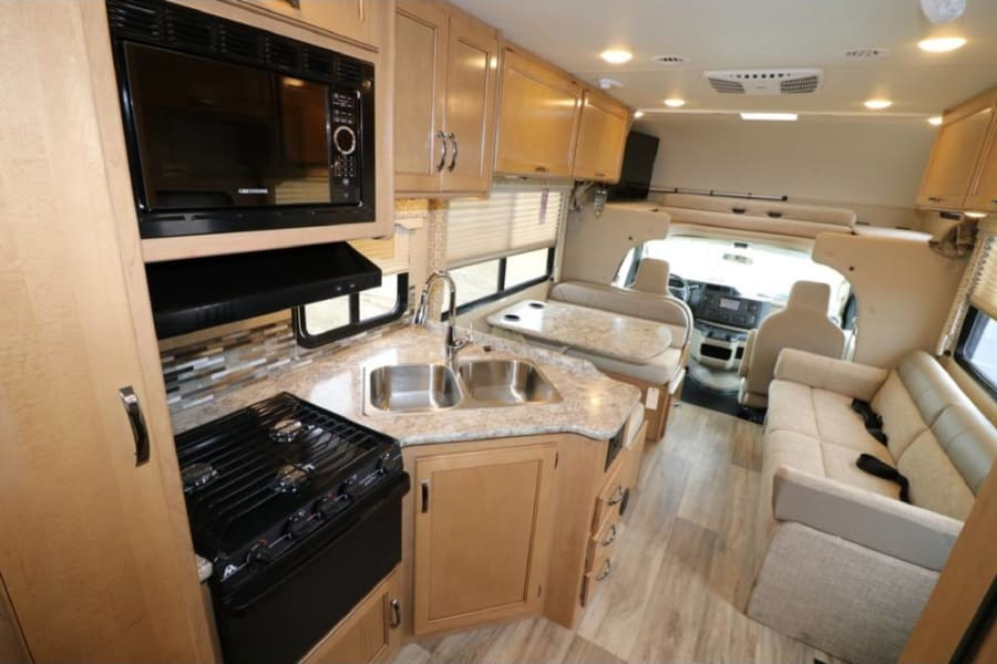 Well equipped kitchen with stove,  oven,  microwave,  double sink,  and refrigerator/ freezer.