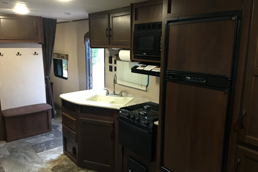 Kitchen area.  Microwave, 3 Burner Stove, Oven and Sink.