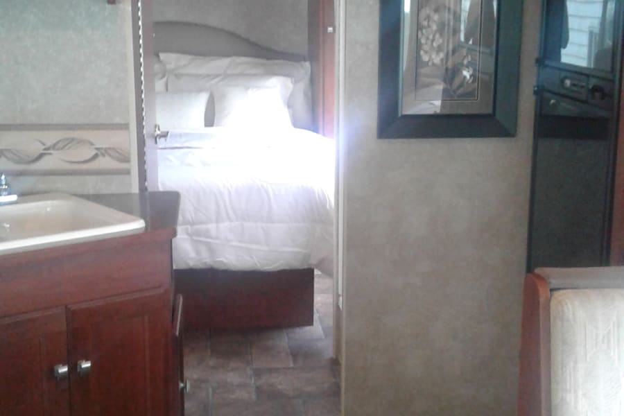 Southern Comfort Queen side bed with fresh crisp hand pressed linen, close door become a master bedroom with bath. Picture come to view when slide is out.