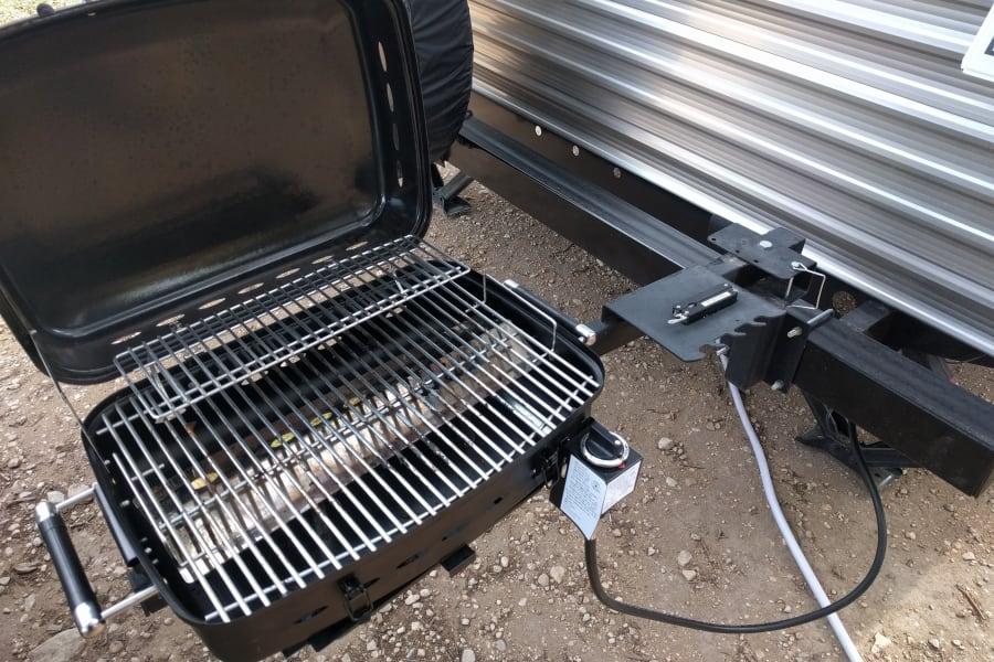 Grill with quick-disconnect propane connection slides onto bumper arm.