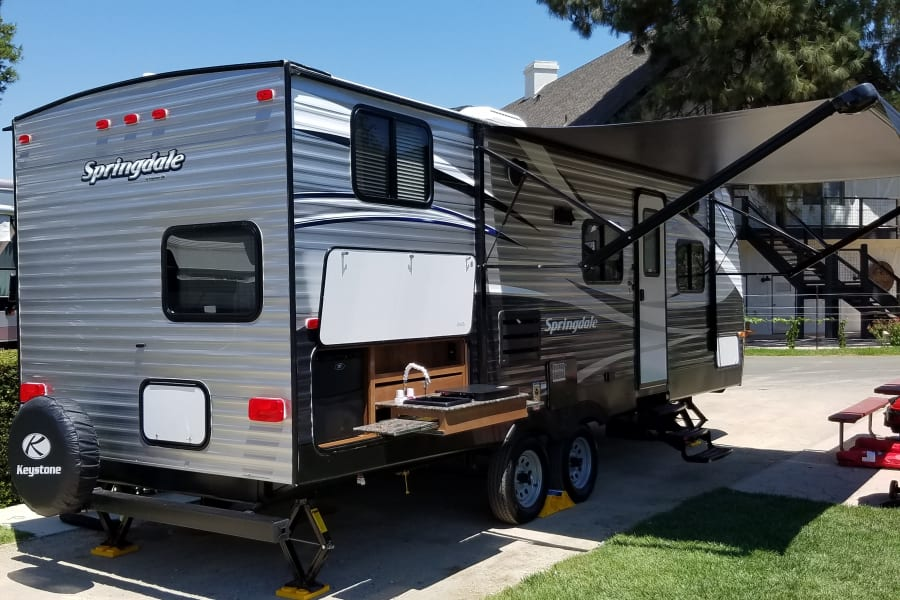 Outdoor kitchen, electric awning, plenty of storage and outdoor shower. Rental includes chairs, lawn rug, Coleman gas BBQ grill, Ice maker, chairs, and much more.