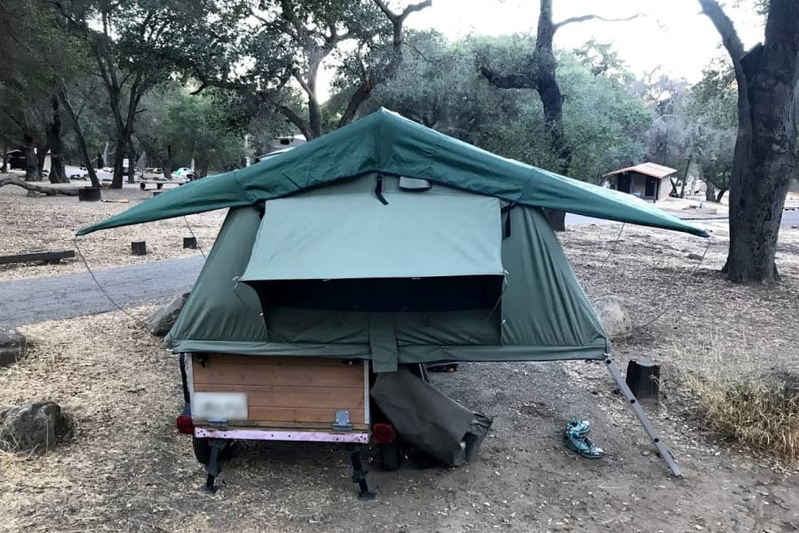 "This 94"" x 55"" tent folds sits on top of a 40"" x 48"" x 24"" storage box on a small trailer."