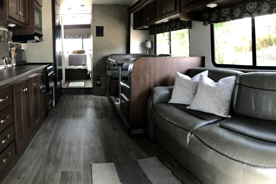 Our 2018, very modern home on wheels still smells new! Look how much light there is all the way to the back in the bedroom. Easy to drive and gets about 15 miles to the gallon! A cooks dream with a very large gourmet counter. The master bed is fluffy with wonderful linens. We have lots of included extras.