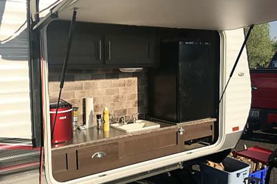 Outdoor kitchen with propane grill, sink, storage, and mini-refridgerator.