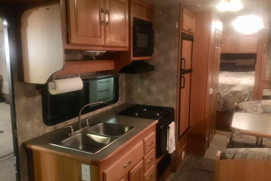 Large functional kitchen with refrigerator/freezer, 3 burner stove top, propane oven and double sink. Fully stocked with plates, silverware, cooking utensils, pots and pans, glasses, coffee cups, single use Keurig, and more.