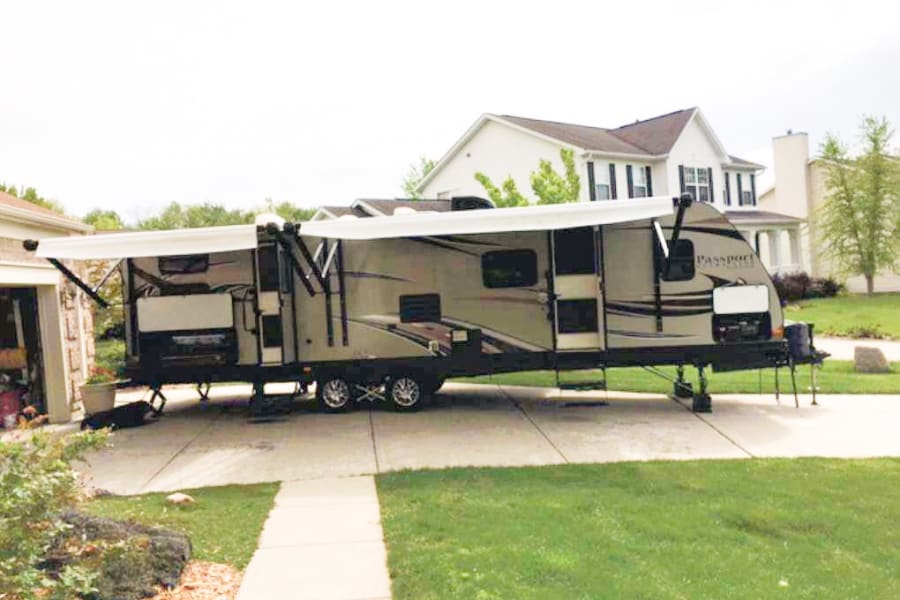 An outdoor view of the trailer. Take note of the large awnings, two entry doors and outdoor kitchen.