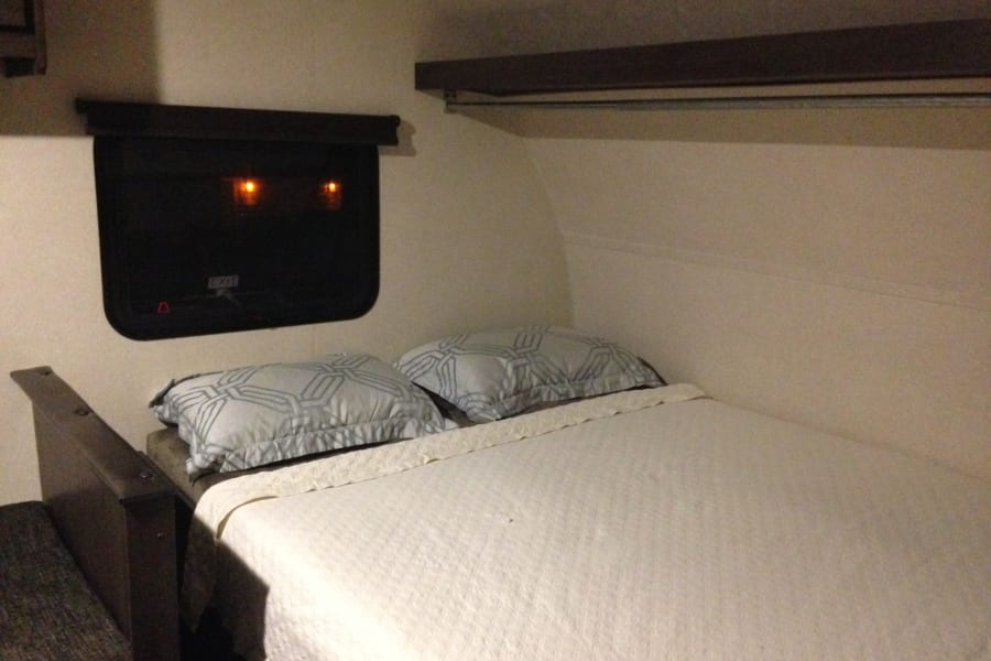 """Queen bed up front with plush """"Teddy Bear"""" mattress and plenty of storage below. Pop open the window and let the cool night air lull you to sleep. Or snuggle up close under the warmth of the furnace on those cold nights away and sleep comfortably knowing the morning frost is a doorstep away."""