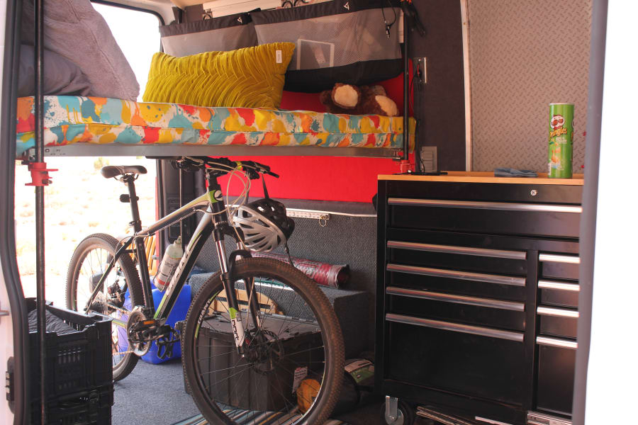 Large kitchen area with bed raised for storage of bikes below.  See other photo of bed lowered.  This photo shows the space without the third seat which is removable.