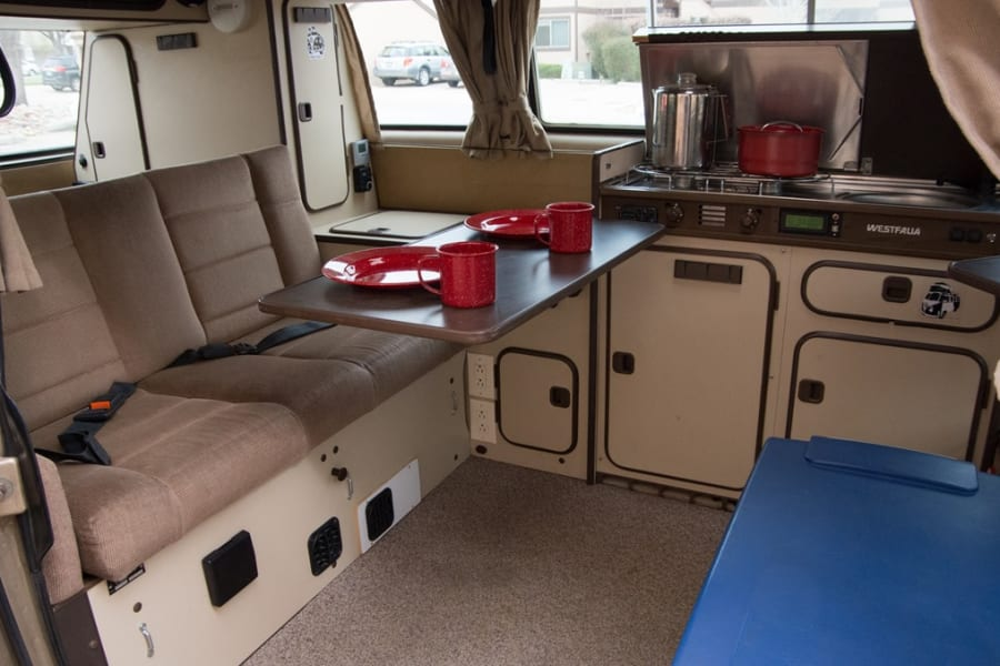 Basic interior, seat folds into a bed, kitchenette with two burner stove, fridge, and sink shown
