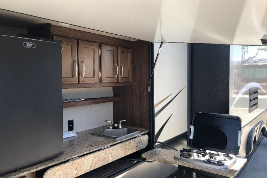Outdoor kitchen.  Includes bar size fridge, sink and gas stove
