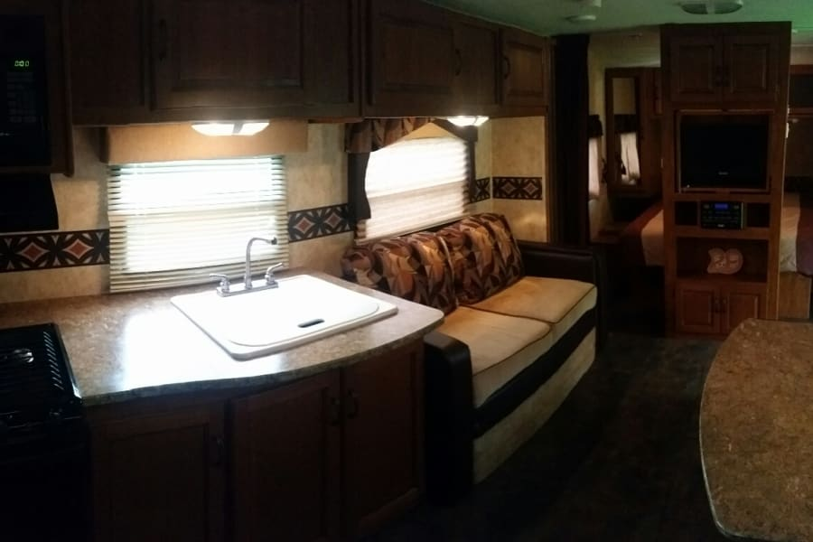 Stove and microwave, very large kitchen sink, sofa is small  (about 5' long), floor to ceiling entertainment center. TV , DvD player, and radio.