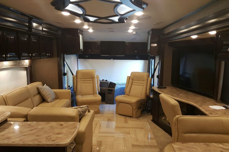 Front lounge area, 32 inch screen TV over driver area, 60 inch screen TV in lounge area with fireplace, work station desk area.
