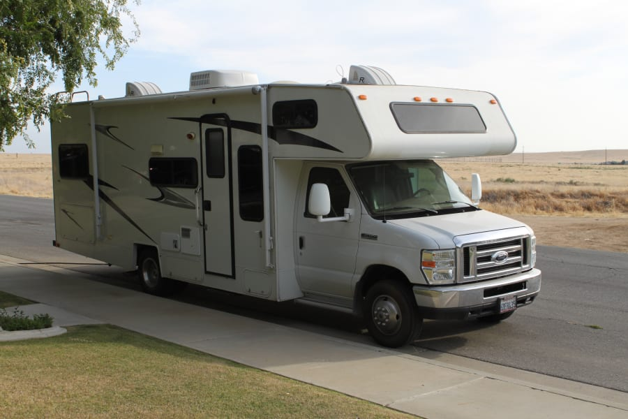 Curb side of the RV has storage, a roll down awning and an electric fold out step for easy entry.