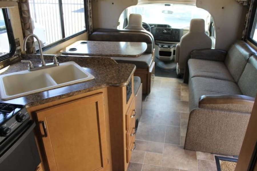 Driver seats, table (bed), couch (bed), kitchen