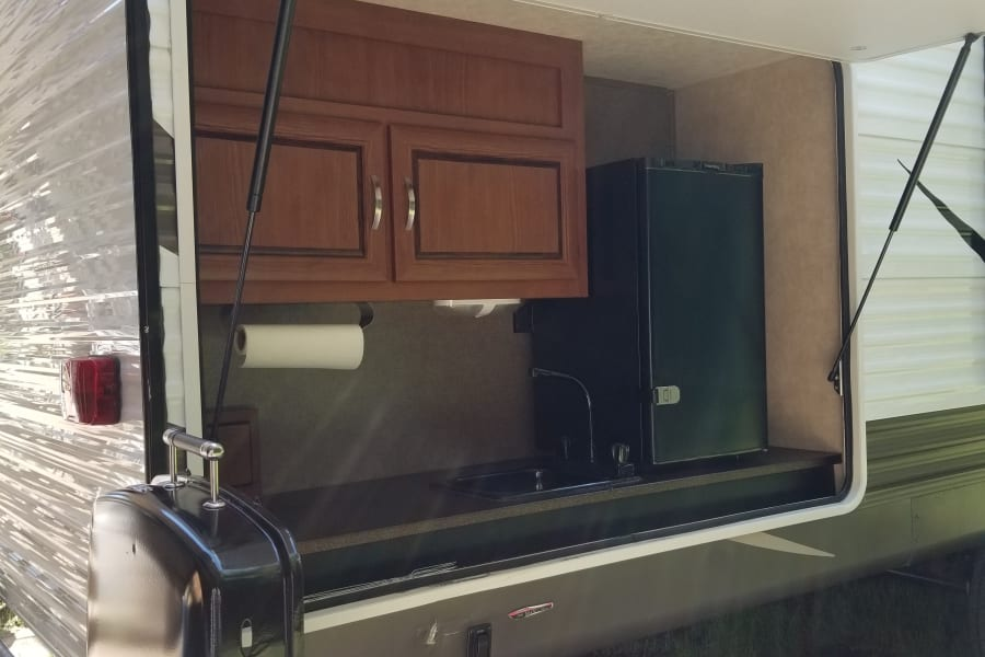 Outdoor kitchen includes mid-size mini fridge, sink, and swing out propane grill.