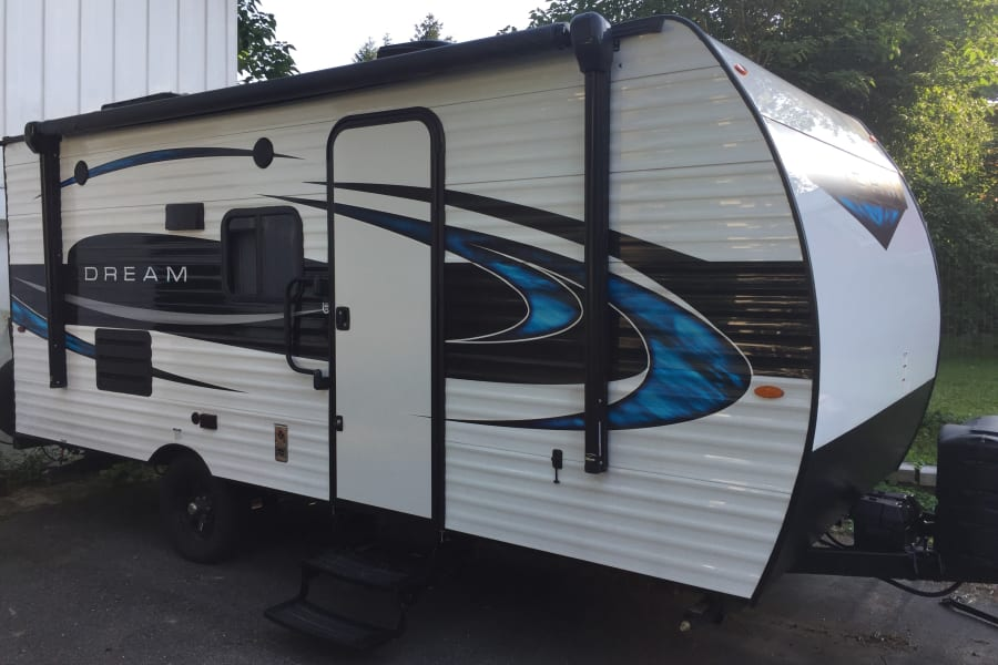 2018 Riverside Dream. The awning rolls out and back in with the push of a button, and there's is a light strip under the awning for outdoor light. The speakers outside are part of the blue tooth stero that you can connect to your phone and your favorite music.