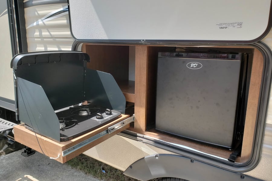 Outdoor kitchen with two gas burner stove and mini fridge.