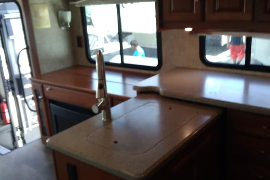 kit sinks ,counter top and cabinet where TV pops up