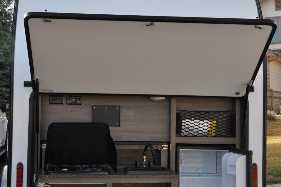 Outdoor kitchen w/2 burner cooktop, microwave, refrigerator, sink and storage