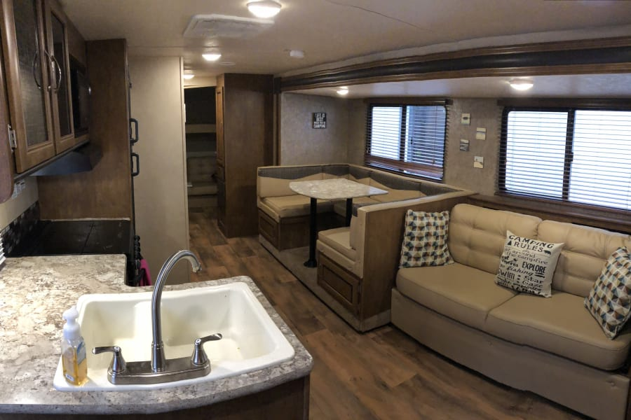 The open concept in the common area of the camper is spacious and comfortable with a large slide out, and ample storage.