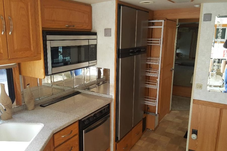 Great equipped kitchen with microwave/convection combo with 4 burner stove and solid countertops