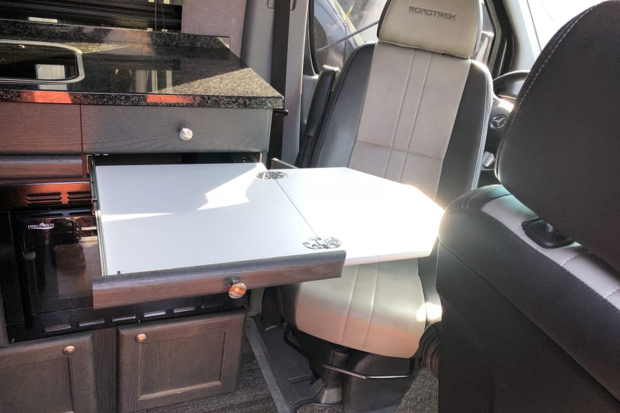 Driver's seat swiveled to pop out desk.