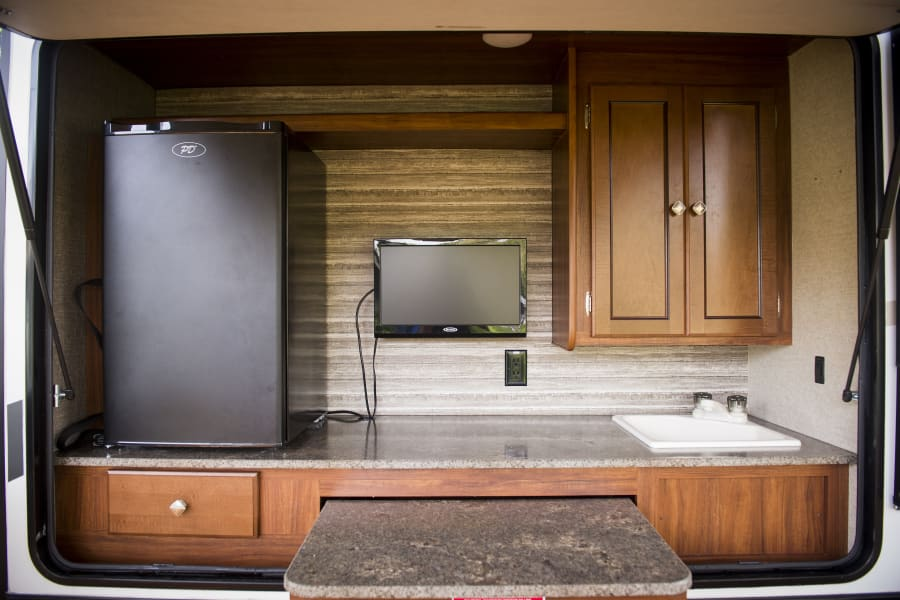 Outdoor kitchen with fridge, tv, fully plumbed sink, and extra prep space.