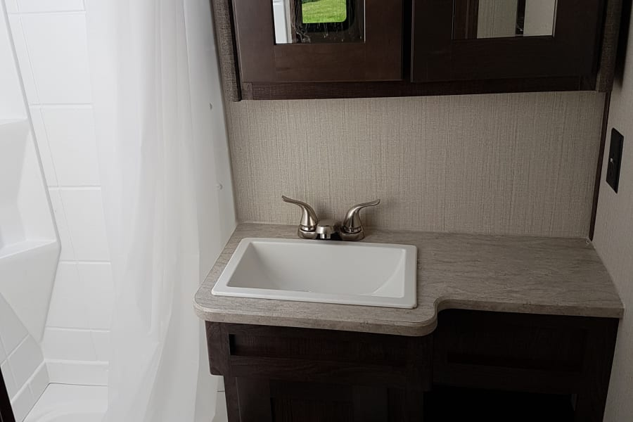 Bright, modern bathroom with shower/tub combo for convenient bathing of all family members (big & small)