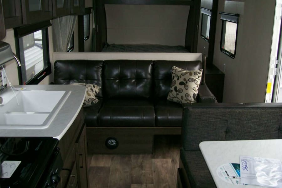 Inside pic of sofa and queen bed in the back
