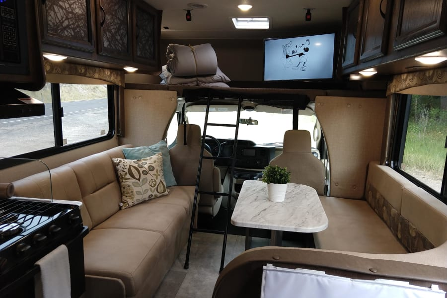 Dining and Sofa with TV and bunk over the cab.