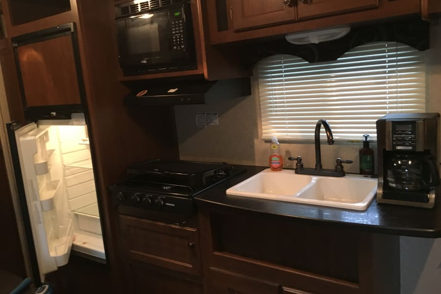 refridgerator n freezer, propane stovetop, double sink, microwave, and coffeemaker