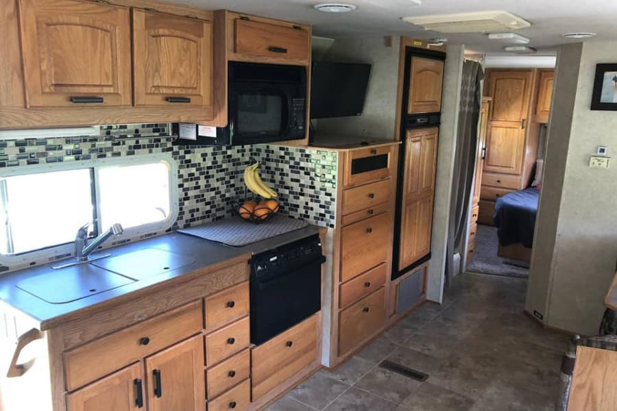 "Updated kitchen includes double sink with spray faucet, 3 burner gas stovetop, oven, microwave, generous fridge and freezer. Wall mount 24"" TV extends to view from dining area and sofa. Coffee pot and toaster are on board for your convenience."