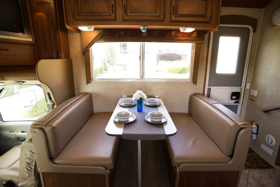 Dining table. Rv comes equipped with a full dinner setting for 6 people.