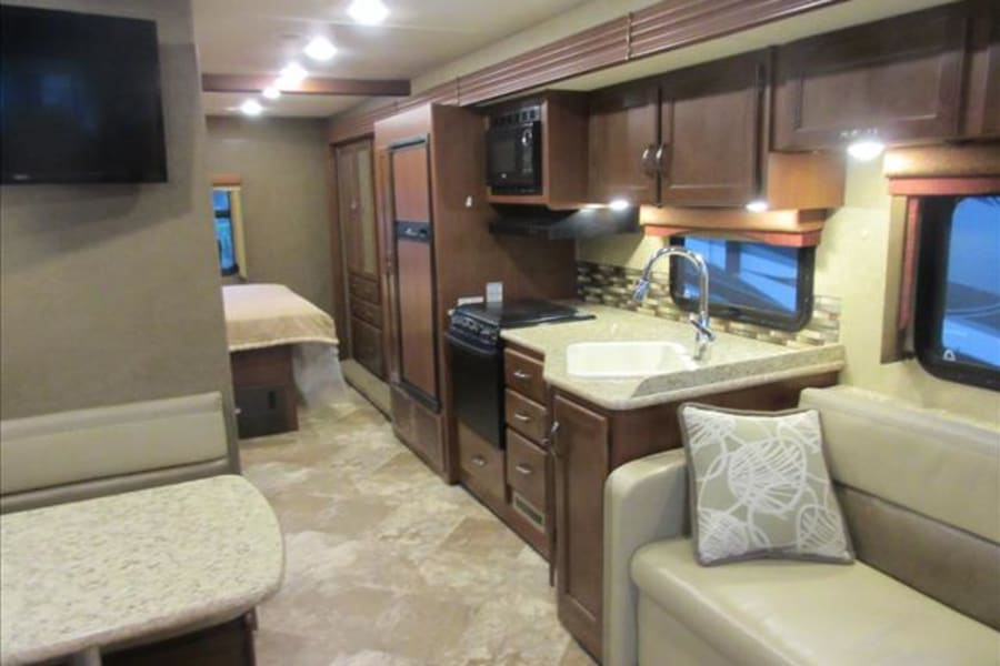 The view you get when you step into the bus is that of a home away from home! You see one of the 3 TVs this RV has to offer as well as a beautiful kitchen equipped with plenty of storage space, a gas stove, microwave, refrigerator, and sink.