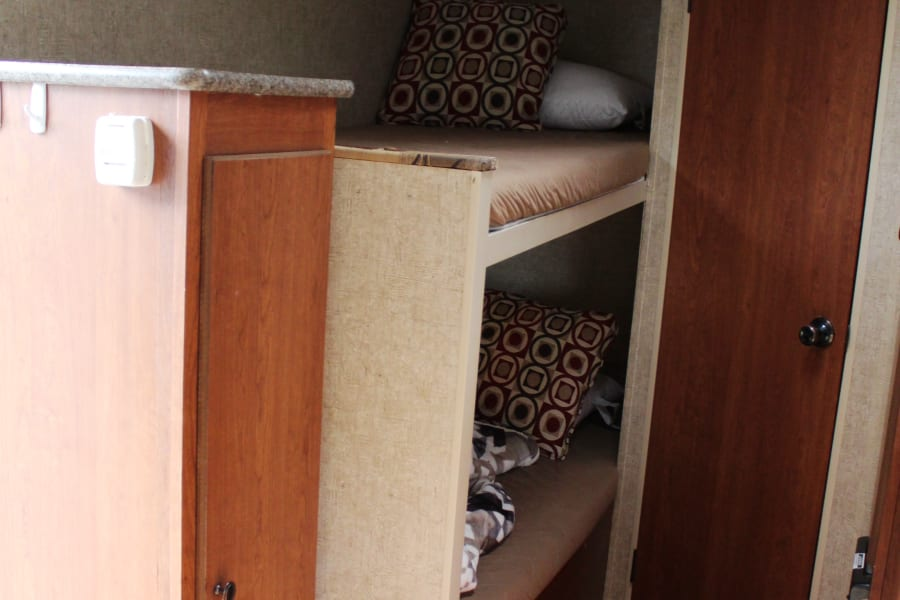 Two large clean bunk beds, bottom bed has a window.  Under the bottom bed is access to outside storage.  Bathroom door is on the right with a toilet and a shower and a vent.