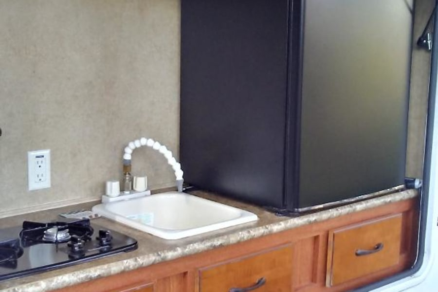 Outside kitchen with gas stove, sink, and refrigerator.