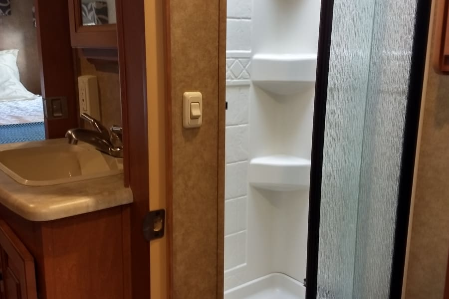 Bathroom with shower and toilet, sink in hallway