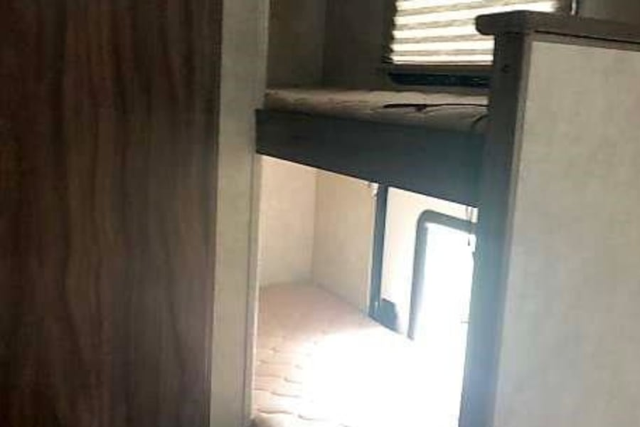 Bunk beds with small storage door to access bunk/storage area from outside