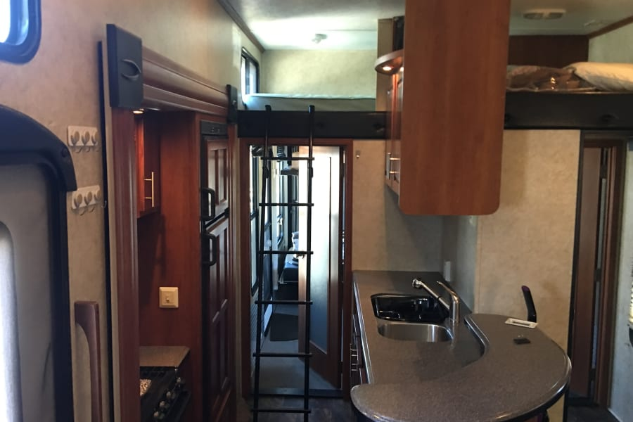 """View of the kitchen and """"crows nest"""" above where someone can sleep."""
